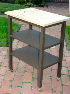 "#344 Metal stand with stone top.  Metal is powder coated to look rusted and there are wheels on the feet. 15"" x 22"" x 28""h"