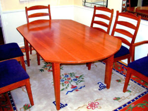 """#43 Cherry oval dining table with tapered legs and an arched apron. reflective of the oval shape.  Includes one 18"""" leaf. Finish:  Hand rubbed tung oil varnish. 72""""x 42""""x 30""""h"""