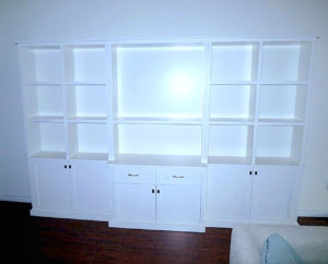 #2006 Bookcase with fixed upper shelves.  Adjustable shelves behind the cabinet doors.  Two drawers to hold DVDs in the center. The lower center section is deeper to accommodate audio equipment