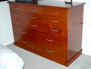 "#311  Maple Dresser featuring 13 drawers.  60"" L x 42""h x 24""d. Drawers vary in depth from 5"" at the top to 10"" at the bottom Finish:  Colonial Maple dye stain and satin lacquer (left) and black lacquer (right)"