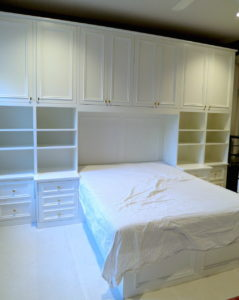 #499 Builtin bed and cabinetry. Custom designed and build bedroom cabinetry.  Features nightstands, additional drawers on either side of the nightstands, adjustable shelves and a large amount of cabinet space with adjustable shelves running across the entire wall.  The bed is recessed in the middle of the unit and there are reading lights above the head of the bed. The finish can be of your choosing