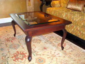 #2007 This lovely coffee table is made of maple with an inset glass panel with a beveled edge. It features a complex moulding profile around the top edge and graceful Queen Anne legs.  Finish:  The maple is lightly distressed with a medium brown stain and satin lacquer.