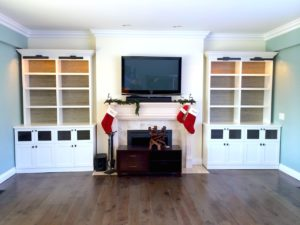 #2005 Breakfront cabinets featuring adjustable shelves behind the doors and metal design panels in the smaller doors.  Fixed shelves with grass cloth on the back wall and topped with crown moulding
